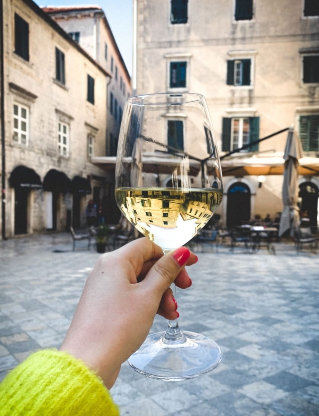 Old town Kotor square architecture view reflecting in wine glass in woman hand